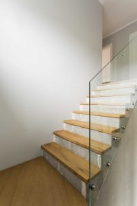 A wooden and concrete staircase with glass balustrade